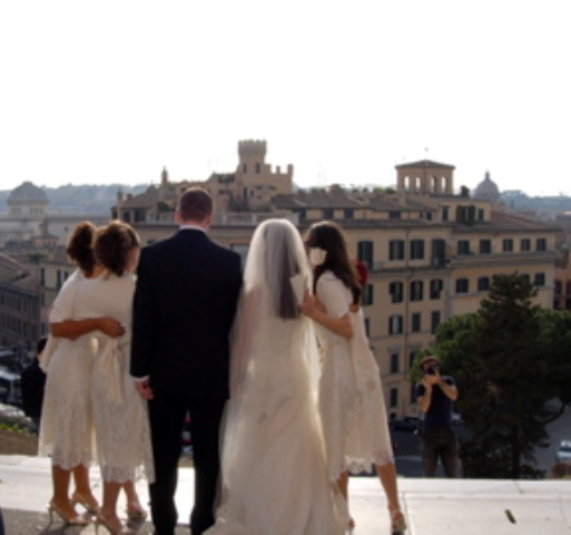 Wedding party posing and looking out at the city view of Rome